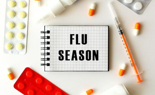 Kladblok met tekst flu seizoen op wit