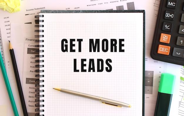 Kladblok met tekst get meer leads op het bureau, in de buurt van kantoorbenodigdheden. bedrijfsconcept.