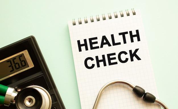 Kladblok met tekst gezondheidscontrole, rekenmachine en stethoscoop. medisch concept.