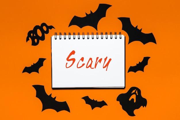 Kladblok met tekst halloween scary op witte en oranje ruimte met vleermuizen, pompoenen en spoken