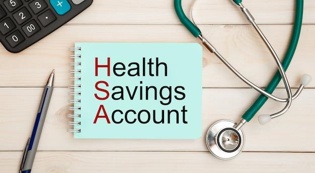 Kladblok met tekst health savings account hsa, rekenmachine en stethoscoop