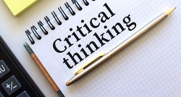 Kladblok met tekst kritiek denken, ernaast ligt een rekenmachine en gele notitieblaadjes