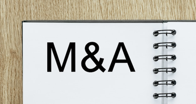 Kladblok met tekst m en a op houten bureau. zakelijk en financieel concept