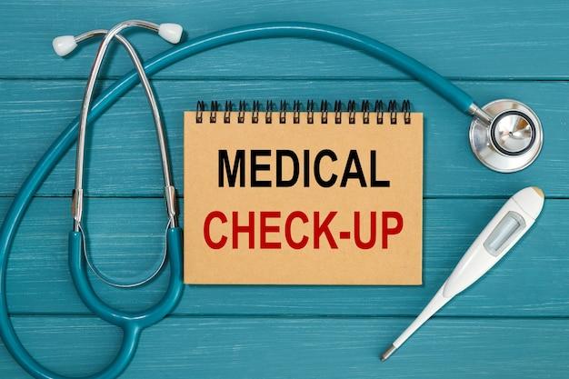 Kladblok met tekst medical check-up en stethoscoop