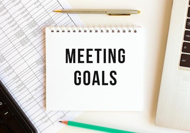 Kladblok met tekst meeting goals op een witte achtergrond, in de buurt van laptop, rekenmachine en kantoorbenodigdheden. bedrijfsconcept.