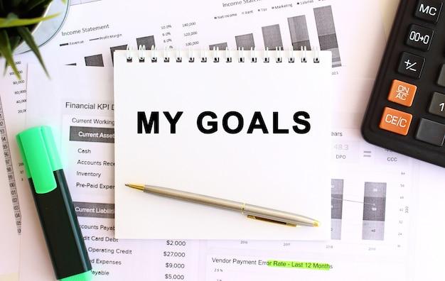 Kladblok met tekst my goals op een witte achtergrond, in de buurt van rekenmachine en kantoorbenodigdheden. bedrijfsconcept.