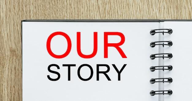 Kladblok met tekst ons verhaal op houten bureau. zakelijk en financieel concept