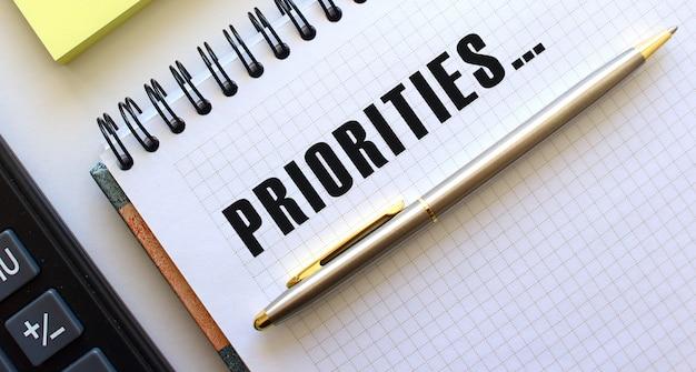 Kladblok met tekst prioriteiten ernaast ligt een rekenmachine en gele notitieblaadjes