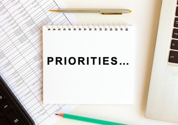 Kladblok met tekst prioriteiten op wit, in de buurt van laptop, rekenmachine en kantoorbenodigdheden.
