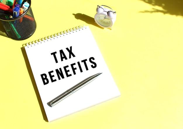 Kladblok met tekst tax benefits met briefpapier. gele achtergrondkleur.