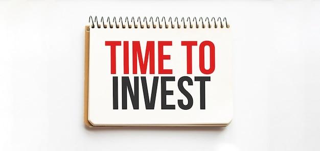 Kladblok met tekst tijd om te investeren. bovenaanzicht