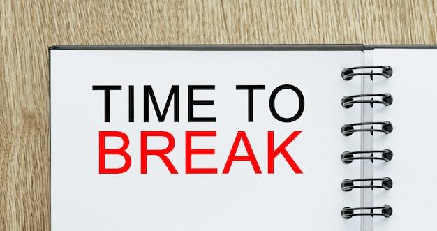 Kladblok met tekst time to break op houten bureau. zakelijk en financieel concept