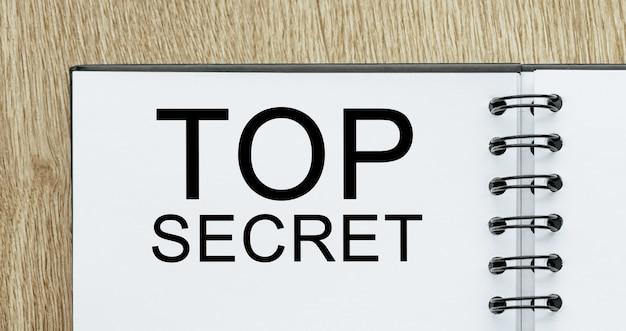 Kladblok met tekst top secret op houten bureau. zakelijk en financieel concept