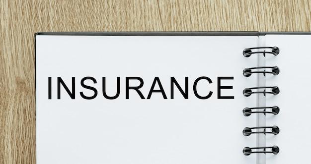 Kladblok met tekst verzekering op houten bureau. zakelijk en financieel concept