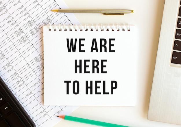 Kladblok met tekst we zijn hier om te helpen op een witte achtergrond, in de buurt van laptop, rekenmachine en kantoorbenodigdheden