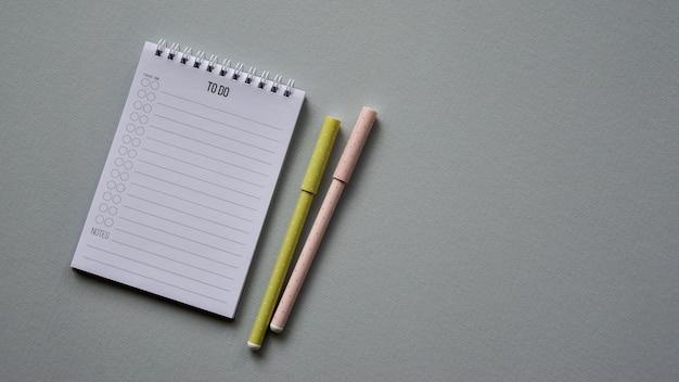 Kladblok met twee pennen op een grijze papieren achtergrond. bovenaanzicht. detailopname. plat leggen.