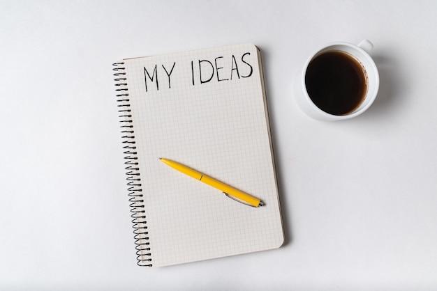 Kladblok met woorden mijn ideeën. pen en kopje koffie. bovenaanzicht.