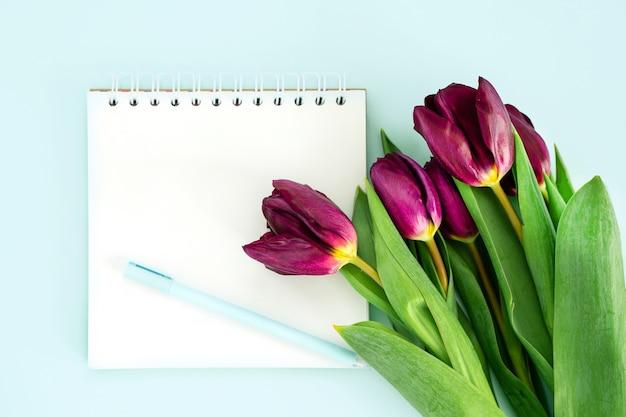 Kladblok om te schrijven en bloemen van tulpen op een pastelblauwe achtergrond, ruimte voor tekst
