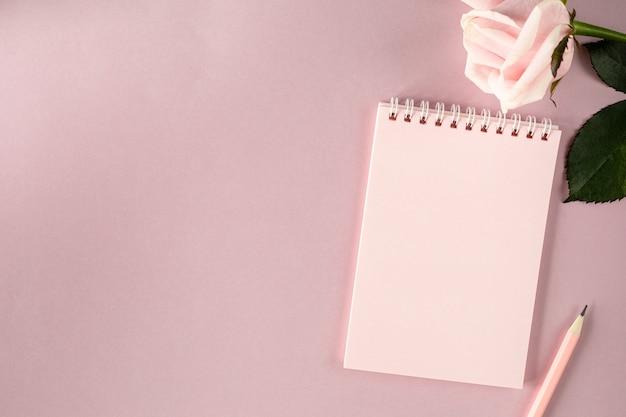 Kladblok op een lichtroze ondergrond met roze roos