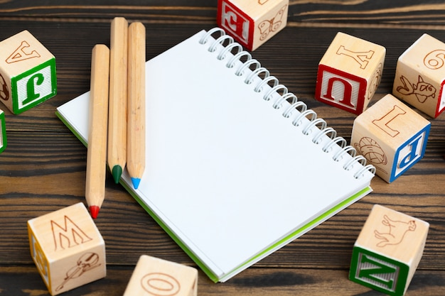 Kladblok op houten tafel en houten alfabet blokken