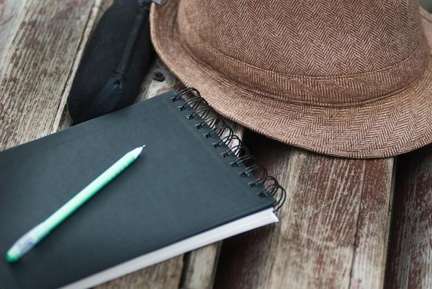 Kladblok, pan, brillenkoker en hoed op bankje in park close-up