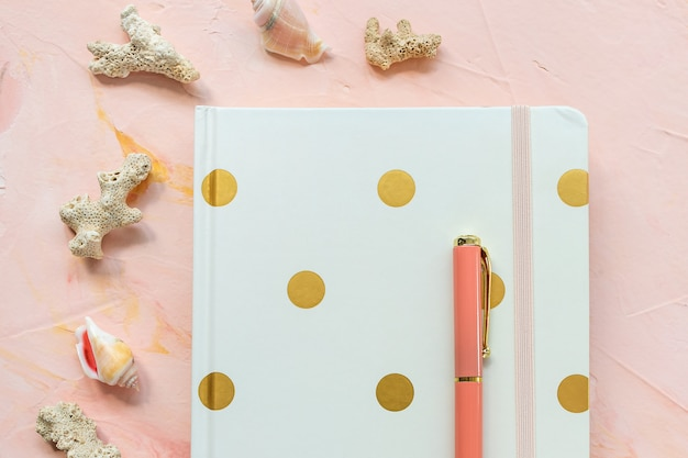 Kladblok, pen, schelpen en koralen op bureau werkruimte, roze backround. plat lag, bovenaanzicht, koptekstsjabloon voor sociale media-held. zee vakantie en zomervakantie planning concept