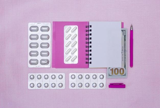 Kladblok, pillen en geld op een roze