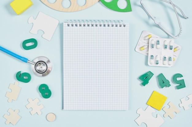 Kladblok, stethoscoop, pillen en speelgoed op een blauwe achtergrond