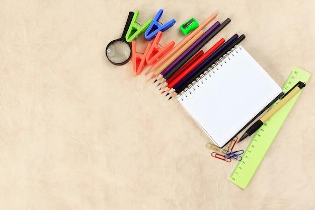 Kladblok voor het maken van aantekeningen en schoolbenodigdheden op een papieren achtergrond .photo met kopieerruimte.