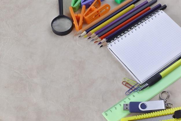 Kladblok voor het maken van aantekeningen en schoolbenodigdheden op een papieren achtergrondfoto met kopieerruimte
