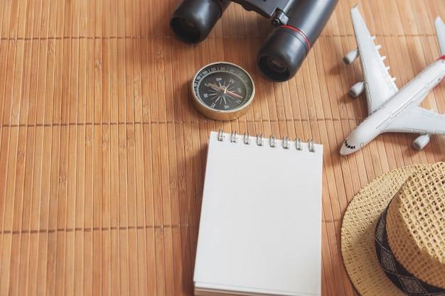 Kladblok voor notitie met paspoort, verrekijker, potlood, kompas, vliegtuig op papieren kaart voor afbeelding van ontdekking van reisavontuur
