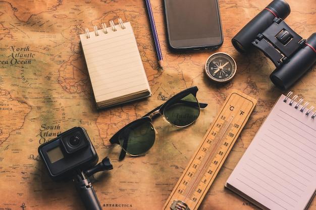 Kladblok voor notitie met verrekijker potlood, kompas op papieren kaart