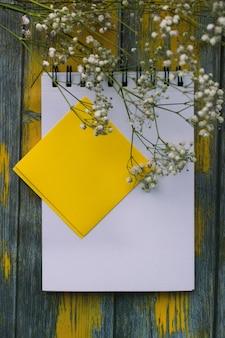 Kladblok voor notities en witte bloemen op een gele achtergrond, bovenaanzicht