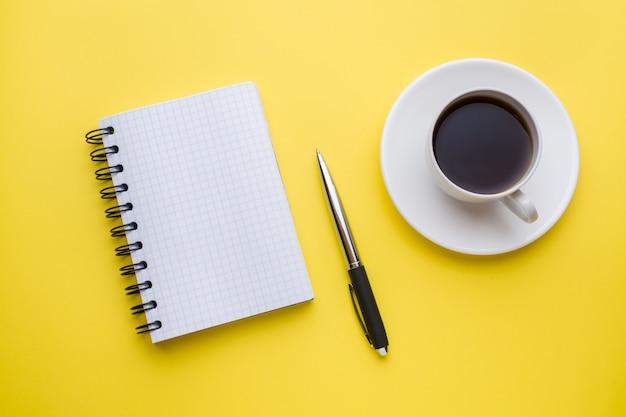 Kladblok voor tekst en kopje koffie gele tafel met kopie ruimte. onderwijs en kantoor concept