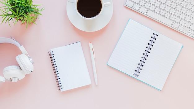 Kladblokken en koffiekopje in de buurt van hoofdtelefoons en toetsenbord