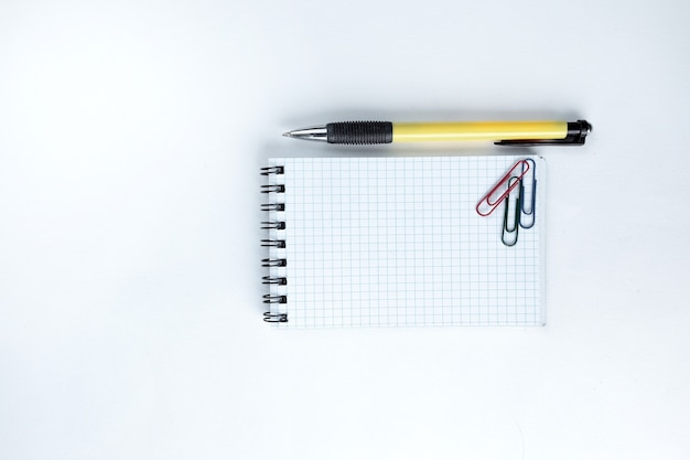 Kladblokpen en paperclip op witte achtergrondfoto met exemplaarruimte