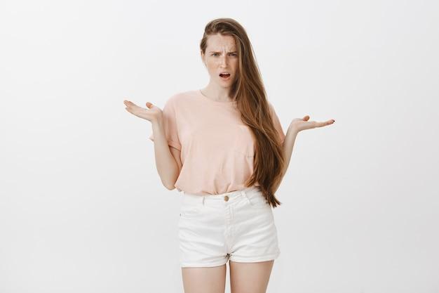 Klagen gefrustreerd tienermeisje poseren tegen de witte muur