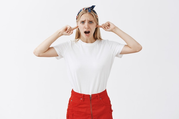 Klagen gehinderd jong blond meisje poseren tegen de witte muur