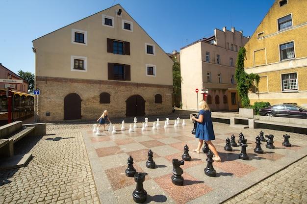 Klaipeda, litouwen jonge vrolijke vrouw en klein meisje houden schaakstukken in hun handen