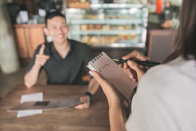 Klant bestelt eten richting serveerster in het restaurant
