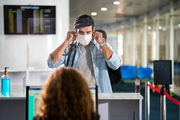 Klant checkt in met gezichtsmasker om te beschermen tegen coronavirus bij luchtvaartmaatschappijservicebalie op luchthaven