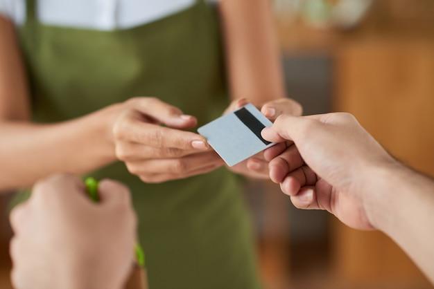 Klant die creditcard geeft aan winkelbediende bij het betalen voor aankoop, selectieve focus