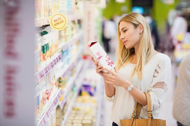 Klant die een fles vruchtensap bekijkt