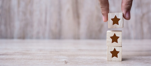 Klant die houten blokken met het drie sterrensymbool houdt.