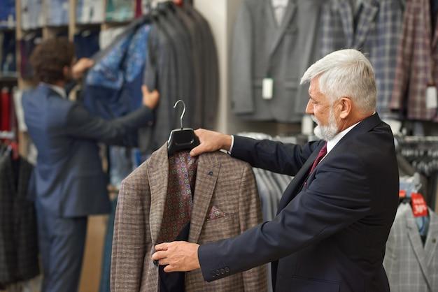 Klant die overweegt geruit bruin jasje te kopen.
