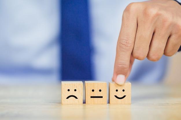 Klant die smileygezicht emoticon op houten kubus drukken