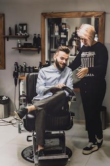 Klant die tijdschrift toont aan kapper
