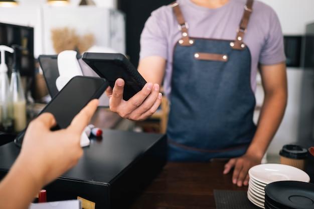 Klant doet contactloze betaling met telefoon in café.