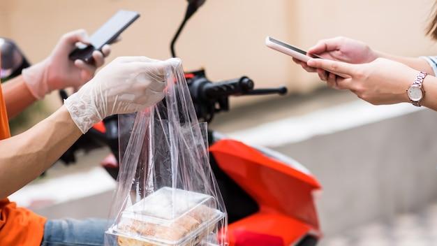 Klant drukt op betaling en bevestigt om eten te ontvangen op smartphone met bezorger