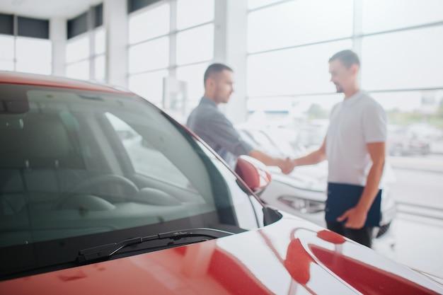 Klant en verkoper staan achter rode auto en schudden elkaar de hand